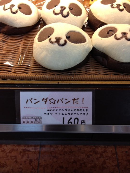 """For those of you who can't Japanese, I'm going to attempt to explain why this is so cute! Basically the sign says """"this is panda bread"""" which doesn't sound all that great, until you know that it reads """"panda pan da!"""" which is a very cute little play on words :) The first 'panda' is written in the script used for foreign words and means 'panda'. the second 'pan da' part uses the foreign language script for 'pan' (bread) and then the normal script for the 'da' (this is). Does that make sense? If not, just know that it's a sweet little word play that tickled me :)"""